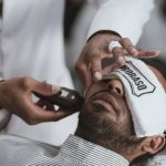 barber trimmig beard of man lying on chair